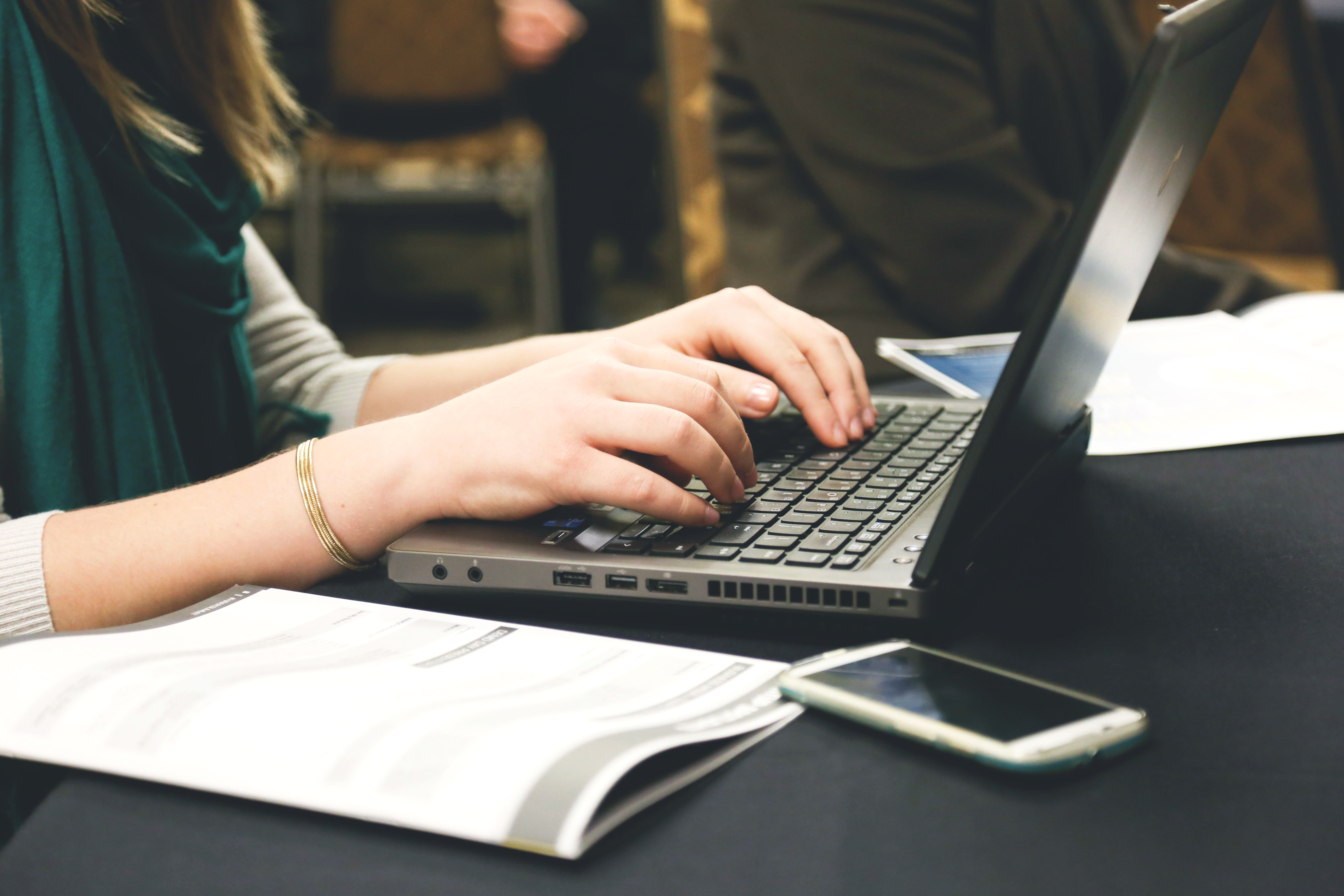 Photo of a woman typing on a laptop computer.
