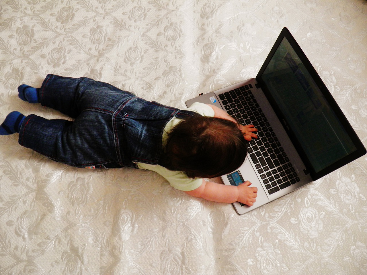 Photo of a baby lying on a bed with a laptop computer.