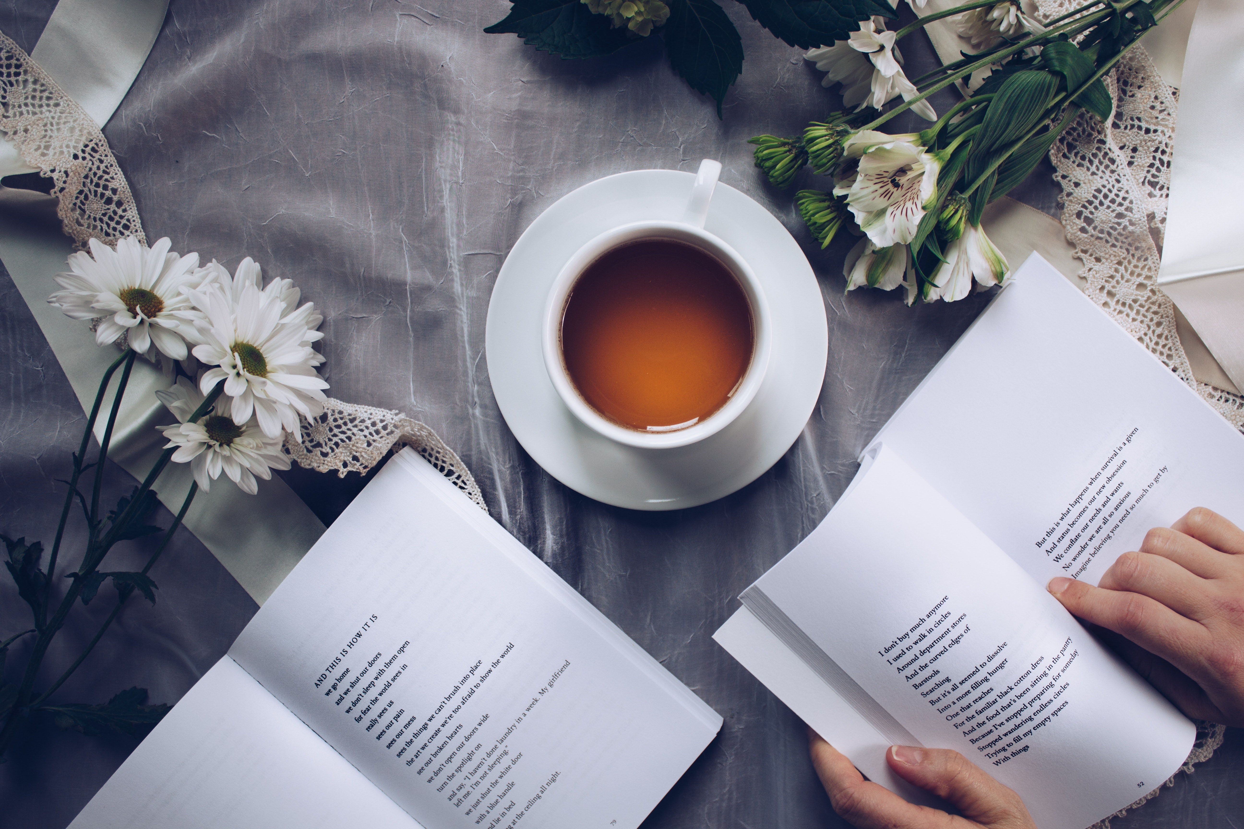 Photo of poetry books with a cup of tea and flowers.